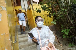 A doctor wearing a protective mask walks after an interview in the low-income neighborhood of Las Mayas, as cases rise amid the…