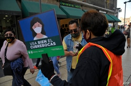 "A worker of the Tourism Secretariat with a sign reading ""Use the face mask correctly"" offers antibacterial gel to pedestrians…"