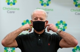 US President-elect Joe Biden adjust his facemask after receiving the second course of the Pfizer-BioNTech Covid-19 vaccine on…