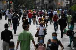 People wearing masks amid the new coronavirus pandemic walk on Sabana Grande boulevard in Caracas, Venezuela, Wednesday, June…