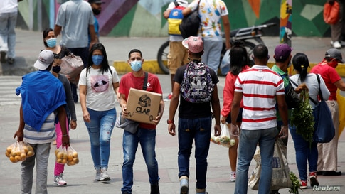 People wearing protective masks walk near street vendors and do not maintain social distancing at the Petare slum during a…