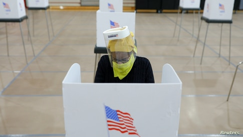 Jocelyn Bush, a poll worker at the Edmondson Westside High School Polling site, cleans each station after a ballot is cast,…