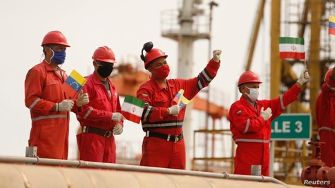 Workers of the state-oil company Pdvsa holding Iranian and Venezuelan flags greet during the arrival of the Iranian tanker ship…