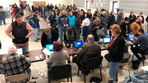Voters wait in line for the North Dakota Democratic presidential caucus in a union hall in Fargo, N.D., on Tuesday, March 10,…
