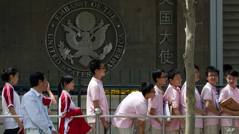 FILE -- In this May 2012 file photo, Chinese students wait outside the U.S. Embassy for their visa application interviews in…