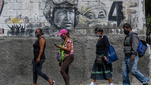 People wear face masks as they walk by a mural depicting Venezuela's late President Hugo Chavez, in downtown Caracas on August…