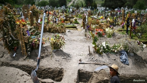 A cemetery worker digs new graves at the Xico cemetery on the outskirts of Mexico City, as the coronavirus disease (COVID-19)…