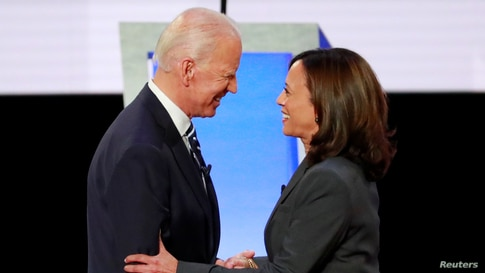 Former Vice President Joe Biden and U.S. Senator Kamala Harris shake hands before the start of the second night of the second U…