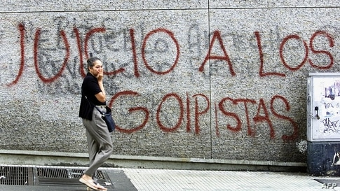 A stranger is seen walking by a wall vandalised by protestors in Caracas, Venezuela15 August 2002. Una transeúnte pasa frente…