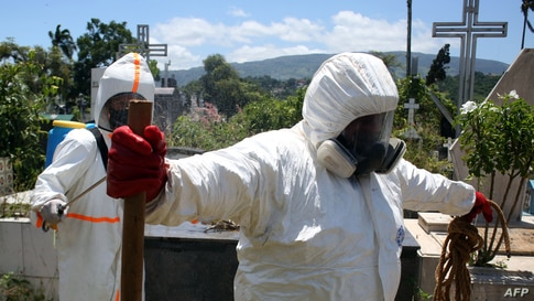Members of Civil Protection disinfect themselves after the burial of an alleged COVID-19 victim at the Municipal cemetery in…