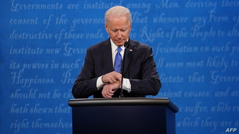 Democratic Presidential candidate and former US Vice President Joe Biden looks at his watch during the final presidential…