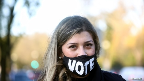 """A woman wears a mask with a sign """"VOTE"""" on the day of the 2020 U.S. presidential election in Washington, U.S., November 3, 2020…"""