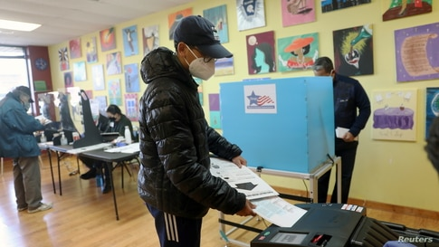 First time voter Logan Walton, 18, casts his ballot at a polling station in Deja Hue Art on Election Day in Chicago, Illinois,…