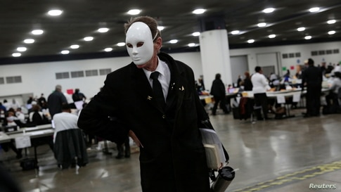 A poll challenger wearing a full face mask reacts while being removed by Detroit Police for causing a disturbance during…