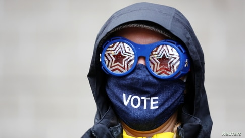 Cesia Kearns wearing glasses and a face mask is seen outside a polling place in the CenturyLink Field Event Center on Election…