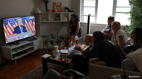 American citizens living abroad watch as U.S. President Donald Trump speaks about early results from the 2020 U.S. presidential…