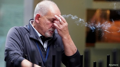 A man smokes a cigarette outside the New York Stock Exchange in the Manhattan borough of New York City, two days after the 2020…