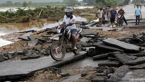 A man drives his motorcycle at a bridge damaged after the passage of Storm Eta, in Pimienta, Honduras November 6, 2020. REUTERS…