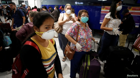 Stranded Ecuadorian tourists, wearing face masks, are pictured while waiting for a new flight after Ecuador's government closed…