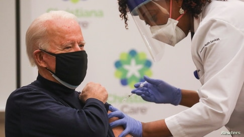 Nurse practitioner Tabe Mase gives U.S. President-elect Joe Biden a dose of a vaccine against the coronavirus disease (COVID-19…
