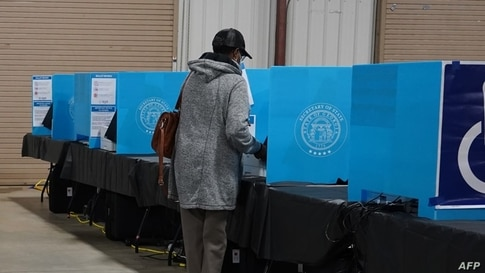 FILE - A Georgia voter marks a ballot during the first day of early voting in the U.S. Senate runoffs at the Gwinnett County Fairgrounds, in Atlanta, Georgia, Dec. 14, 2020.