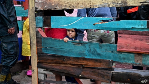 A child looks on as residents are evacuated from their homes amid the arrival of Hurricane Iota, en Tegucigalpa, on November 17…