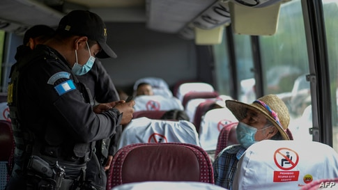 A police officer checks a man's documents on a bus at a bridge in Zacapa, Guatemala on January 19, 2021. - On buses and trucks,…