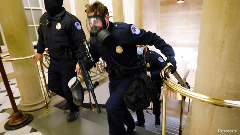 U.S. Capitol police officers take positions as protestors enter the Capitol building during a joint session of Congress to…
