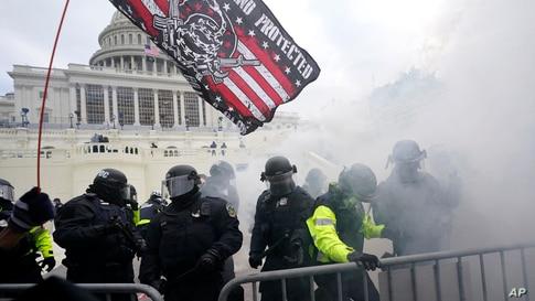 Police hold off Trump supporters who tried to break through a police barrier, Wednesday, Jan. 6, 2021, at the Capitol in…