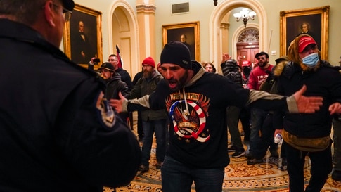 Protesters gesture to U.S. Capitol Police in the hallway outside of the Senate chamber at the Capitol in Washington, Wednesday,…