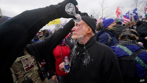 A demonstrator has his eyes flushed with water after confronting police, Wednesday, Jan. 6, 2021, at the Capitol in Washington…