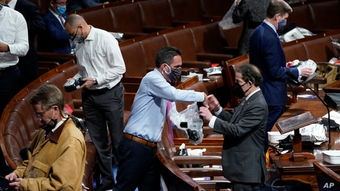 Lawmakers prepare to put on masks on the floor of the House of Representatives as protesters enter the U.S. Capitol, Wednesday,…