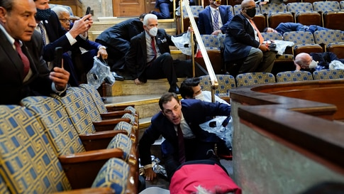People shelter in the House gallery as protesters try to break into the House Chamber at the U.S. Capitol on Wednesday, Jan. 6,…