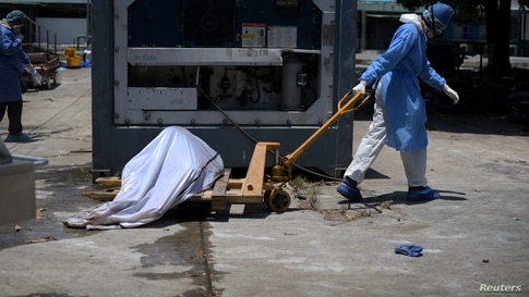 Health workers wearing protective gear bring a dead body past a refrigerated container outside of Teodoro Maldonado Carbo…