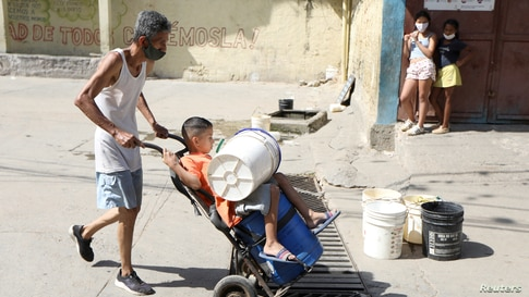 A man carries a child over a wheelbarrow near an unknown water source in the low-income neighbourhood of Petare amid the…