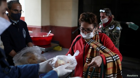 A woman receives bread at a soup kitchen organized at the Caacupe church, during the coronavirus disease (COVID-19) outbreak,…