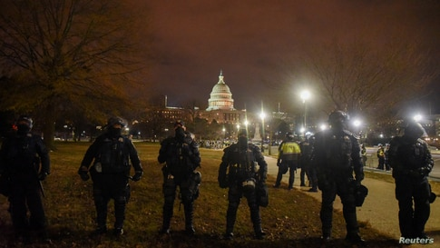FILE PHOTO: Security forces stand guard as the surroundings of the U.S. Capitol are empty during a curfew in Washington, U.S…