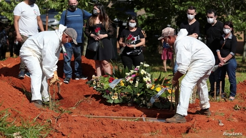Relatives of a man who died from the coronavirus disease (COVID-19) react as gravediggers wearing protective suits bury the…