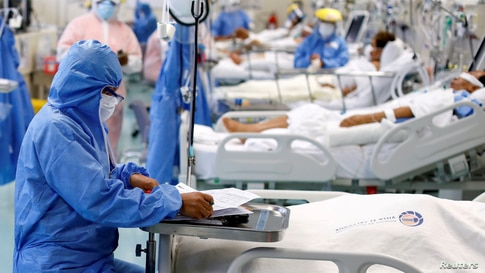 FILE PHOTO: A medical worker takes notes near a patient at the intensive care unit (ICU) of the Emergencias de Villa El…