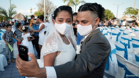 A newly-wed couple takes a selfie as they take part in a collective wedding ceremony celebrated on Valentine's Day, as the…