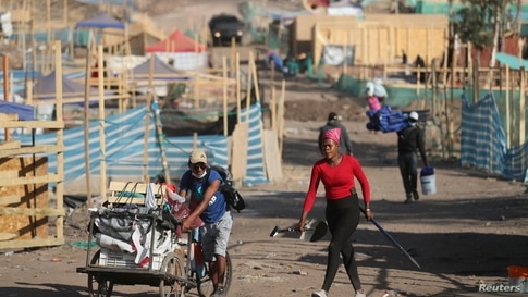 People move their belongings during an eviction of an unauthorized settlement without potable water, drainage system and…