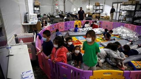 Young unaccompanied migrants, from ages 3 to 9, watch television inside a playpen at the U.S. Customs and Border Protection…
