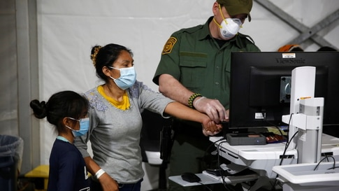 A migrant and her daughter have their biometric data entered at the intake area of the Donna Department of Homeland Security…