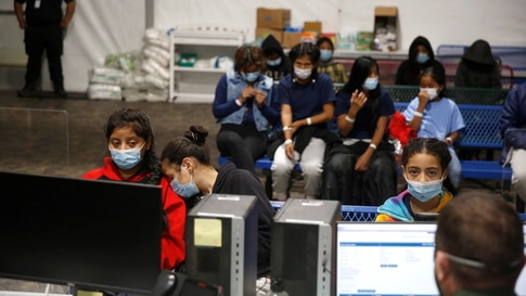 Young migrants get processed at the intake area of the Donna Department of Homeland Security holding facility, the main…