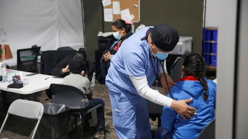 A young migrant gets a medical check-up before entering the intake area at the Donna Department of Homeland Security holding…