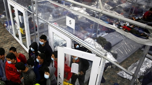 Young migrants talk to an agent outside a pod in the Donna Department of Homeland Security holding facility, the main detention…