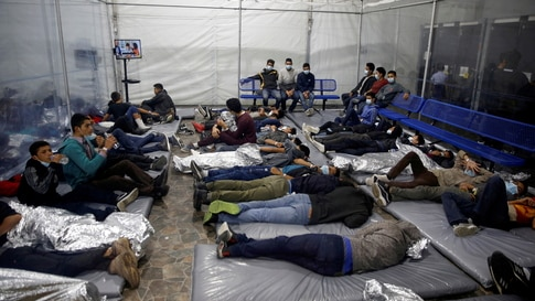 Young migrants lie inside a pod at the Donna Department of Homeland Security holding facility, the main detention centre for…