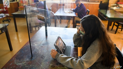 Students work behind protective barriers during an art class as they return to in-person learning at St. Anthony Catholic High…