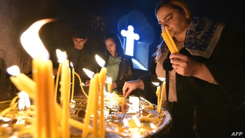 Armenian Christian worshippers light candles during an Easter religious service in Yerevan on April 4, 2021. - Millions of…