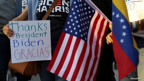 A woman holds a sign as members of the Venezuelan community react after the Biden administration said it would grant temporary…